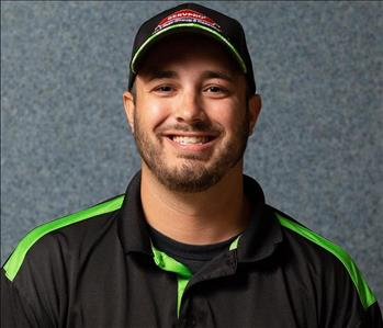 Male employee Ryan poses in a black shirt and hat, SERVPRO logo, light beard