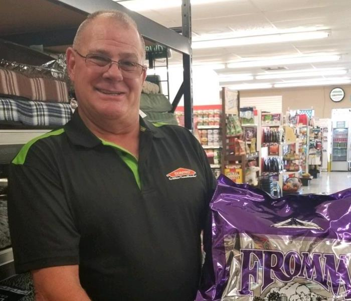 A male SERVPRO employee holding a purple bag of dog food.