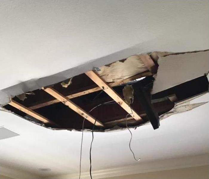 A huge hole in the ceiling of this home with drywall falling to the floor below.