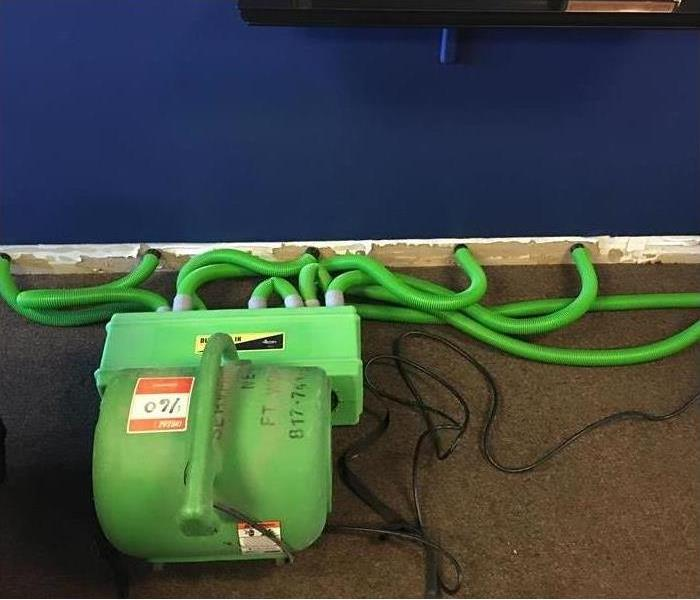 device with green hoses inserted into baseboard area of wall