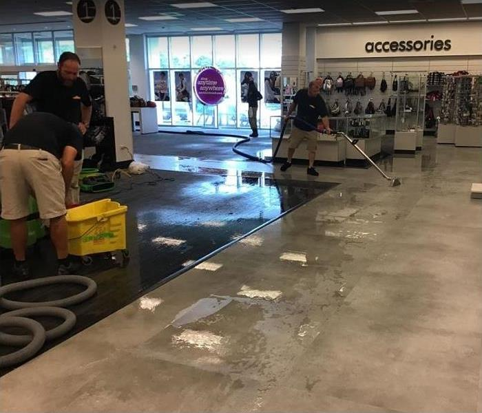 SERVPRO technicians removing standing water from store