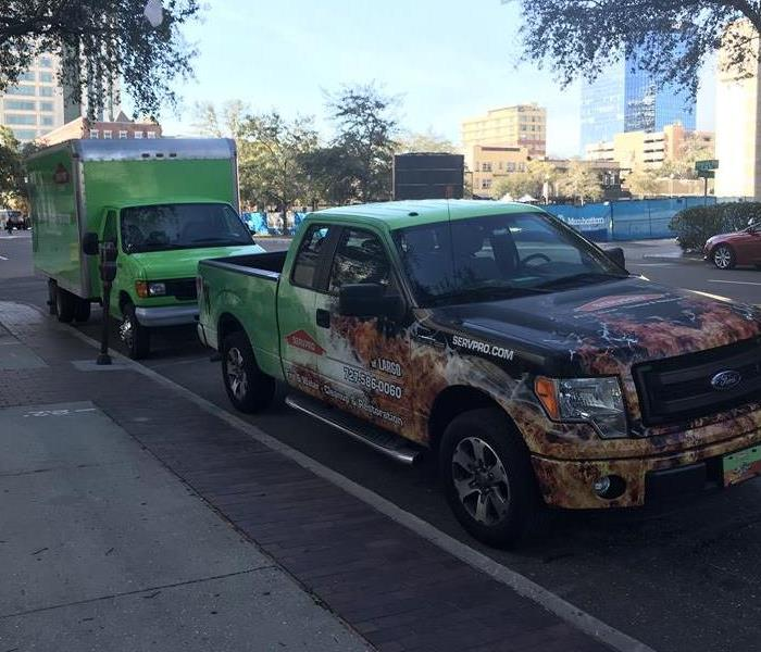 Two SERVPRO vehicles parked on a sidewalk.